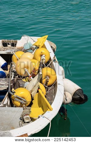 Close up of a small fishing boat with fishing equipment (buoys for the nets) docked in the port - Liguria, Italy