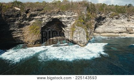 Aerial view of Rocky coast with high cliffs, sea surf with breaking waves on the coast, Nusa Penida, Indonesia. Ocean with waves and rocky cliff. Travel concept