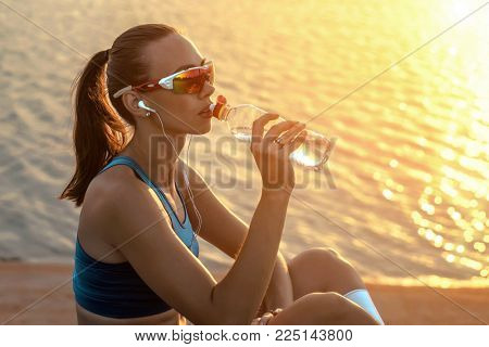Running woman in sport sunglasses drink. Female runner with her bottle with water freshness after training outdoor workout on beach. Beautiful fit mixed race Fitness model outdoors.