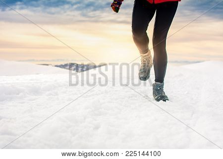 Person hiking on the mountaintop covered with snow low angle view