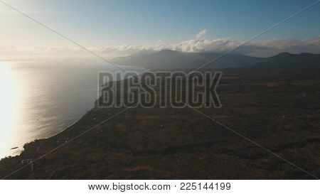 Sea coast at sunrise. Aerial view of sunrise on the ocean coast, mountains, sea, beach, sky, clouds. Bali, Amed, Indonesia. Sunrise on the island of Bali