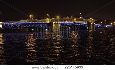 Bridge over the river, illuminating the water with light from lampposts. City night scene with illuminated drawbridge over river. Saint Petersburg, Russia.