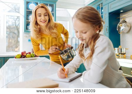I cherish you. Beautiful alert blond young mother smiling and holding a saucepan while looking at her little daughter writing in her notebook