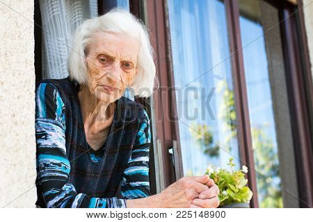 Pensive grandma in her 90s at the home window alone