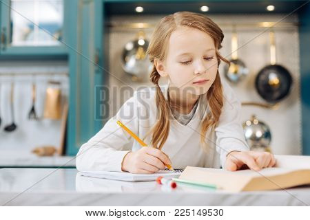Being a pupil. Pretty happy fair-haired girl smiling and writing in her notebook while sitting at the table and reading a book