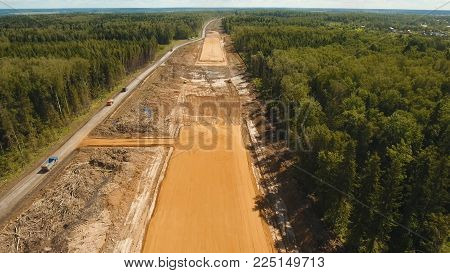 Construction of a new road in the forest area. Aerial view construction road place. Construction machinery for the construction of a road in the forest.