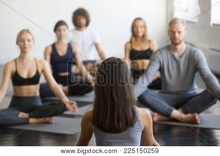 Group of young sporty people practicing yoga lesson with instructor, sitting in Padmasana, Lotus pose, working out, students training in studio, focus at teacher rear view. Wellness, wellbeing concept