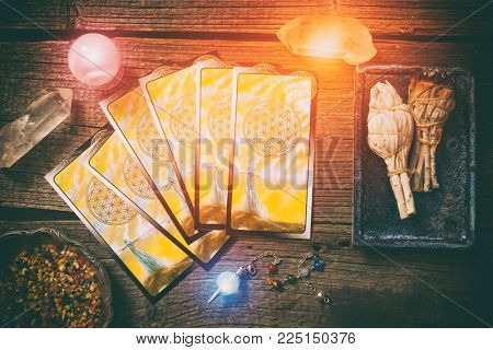 Tarot cards, dowsing tool, incense and crystals on a wooden board