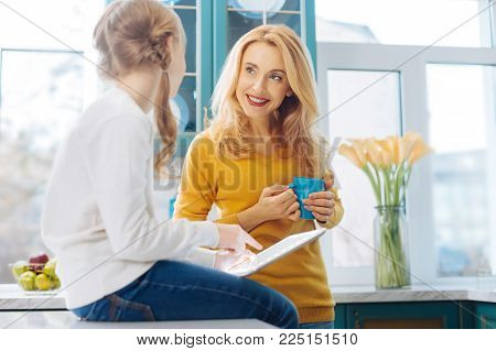 My dear child. Beautiful cheerful blond slim mother smiling and holding a cup of tea and her daughter using a tablet while sitting on the table