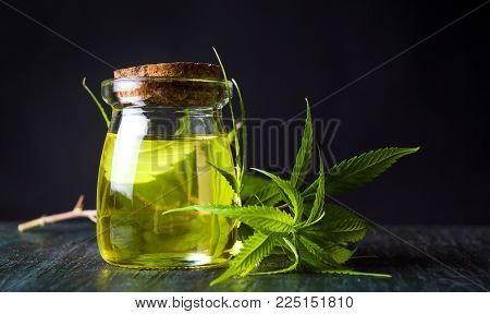 Cannabis oil and marijuana leaves on wooden table