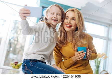In high spirits. Good-looking joyful fair-haired slim mother smiling and holding a cup of tea while her daughter taking selfies