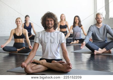 Portrait of friendly smiling yoga instructor looking at the camera, group of young sporty people practicing at yoga lesson, sitting in Padmasana exercise, Lotus pose, students working out in club