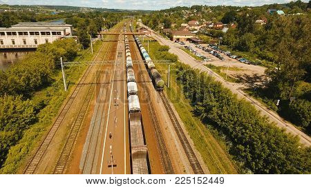 Freight train with cisterns and containers on the railway. Aerial view Container Freight Train, Locomotive in the countryside, Railway and highway.