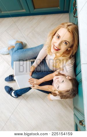 Reading a book. Good-looking joyful fair-haired mother and daughter smiling and sitting on the floor in the kitchen and reading a book