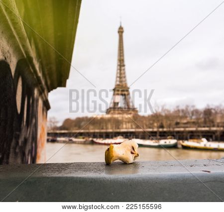 Bitten Apple Core Left On Paris Bridge With Eiffel Tower In The Background With Sun Flare