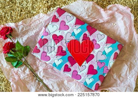 An empty heart-shaped red tag placed on the wrapped gift box along with red roses. A valentine's day gift and background.