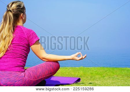 Young girl doing yoga (lotus pose) sitting on a yoga mat on the grass against the background of the morning sea. Concept of health.