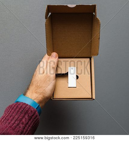 Man holding white ethernet adapter in cardboard box after unboxing