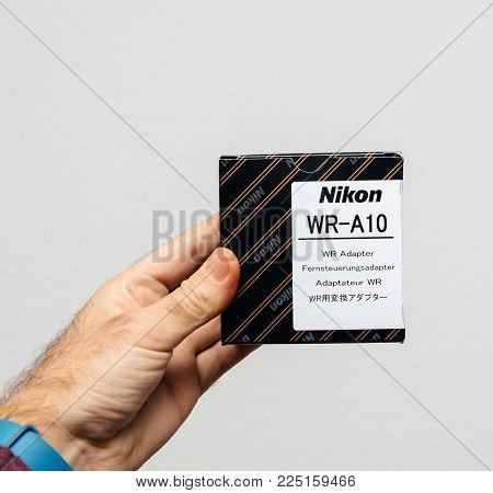 PARIS, FRANCE - JAN 23, 2018: Man holding against gray background a box of Nikon accessory WR-a10 wireless camera flash adapter