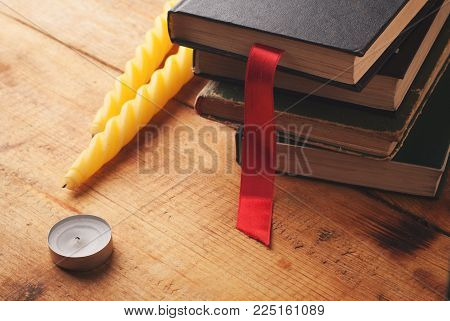 Old hardcover books on a wooden background, yellow candle and a red bookmark in a cozy atmosphere