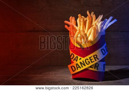 French fries in a red packing box on a wooden table with yellow police ribbons with the word DANGER. Copy space for text