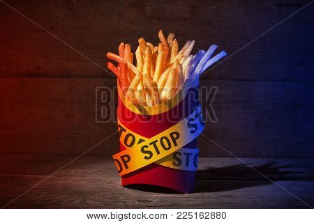 French fries in a red packing box on a wooden table with yellow police ribbons with the word STOP