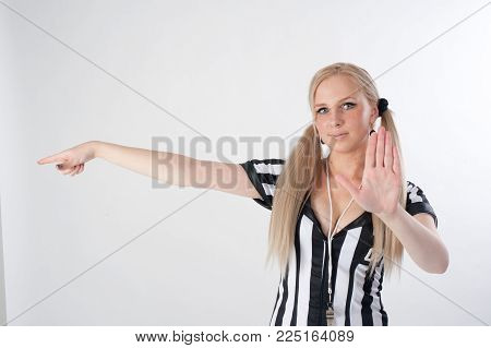 Young attractive referee whistling at white background