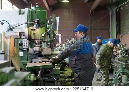 LIPETSK, RUSSIA - JUNE 15, 2017: Lipetsk Machine Tool Plant, A man at work on a vertical milling machine. Machining of a metal part on a metal-cutting machine.
