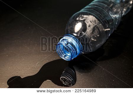 Access to clean water is an empty plastic bottle with spilled water. Photography can illustrate the shortage of clean water or drinking water.