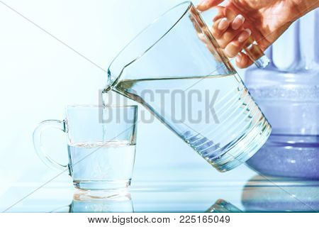 A woman pours clean water from a jug. The concept of water diet and environmental protection.