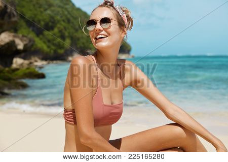 Young Happy Female Wears Sunglasses, Headband And Swimsuit, Poses Against Sea Cliff And Beautiful Bl