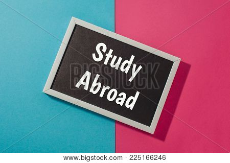 Study Abroad - text on chalkboard on blue and pink bright background.
