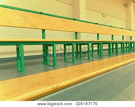 Rows of empty wooden benches in school sporting hall.  Tribune in gym for fans of matches with empty wooden seats.