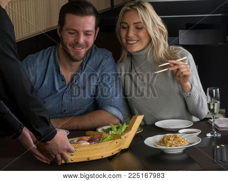 waiter bring the sushi roll boat to a couple in restaurant
