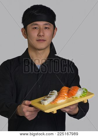 Asian cook hold a set of sushi rolls on wood table.