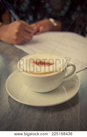 Vintage image young woman drinking  latte at the coffee shop. Girl student working and drinking coffee. A girl writes in a notebook