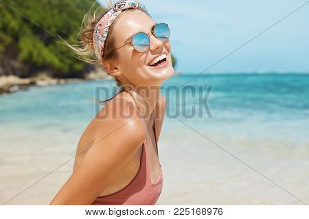Summer Holidays, Vacations And Resort Concept. Beautiful Glad Young Female Wears Swimsuit And Trendy