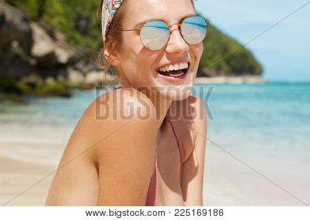 Cropped View Of Pleasant Looking Joyful Female In Trendy Sunglasses, Laughs, Poses Against Beautiful