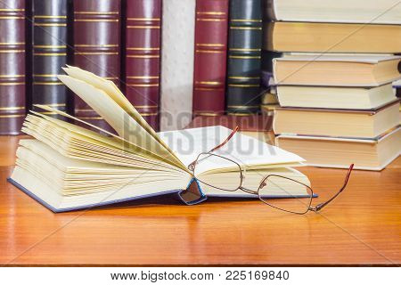 Open book in blue hardcover and classic mens eyeglasses closeup at selective focus with blurred book text on a wooden table against of the other books