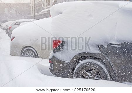 Snow covered ows of cars in the parking lot. Urban scene, snowstorm. Clean automobile from the snow