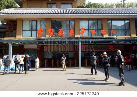 HANGZHOU, CHINA - JAN 18, 2018: Tourists queue to buy the entrance ticket at the ticket booth in Lingyin Temple, Hangzhou. The temple is one of the largest and wealthiest Buddhist temples in China