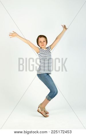 Vertical Portrait Of Jumping Little Girl. Cute Jumping Girl. Cheerful Pretty Young Girl Jumping And Holding Hands Up.