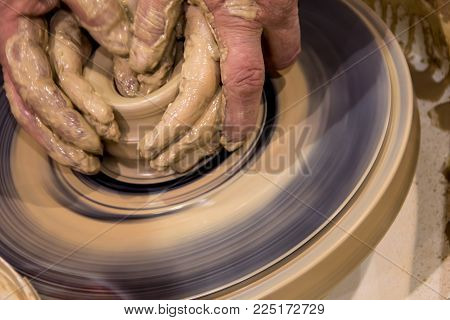 Pottery old fashion crafting. making a jar of raw clay on a potter's machine with men's hands, learning to pottery