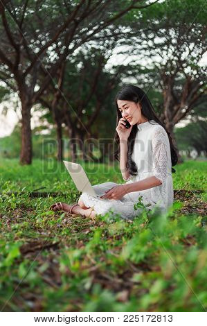 Beautiful Woman Using Laptop And Calling With Mobile Phone In The Park