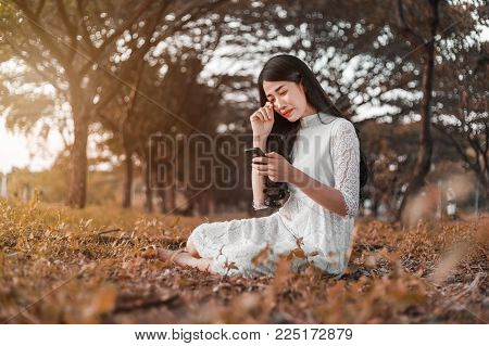 Sad Woman Calling On Mobile Phone In Park
