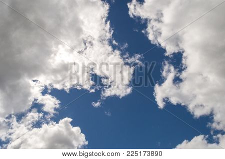 Illuminated fluffy white clouds brightly back lit creating shadows and strong highlights, with a strong blue sky behind them. Beautiful, moody and atmospheric.