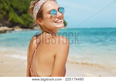 Nature, Tourism And Summer Holidays Concept. Back View Of Slim Attractive Female Traveler Spends Fre