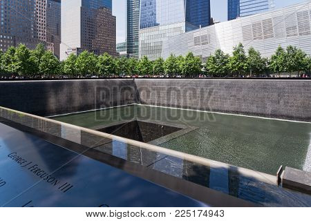 New York, USA - June 08, 2015: South pool memorial commemorating the victims of the 11 september terror attack in 2001. New York architecture in the background.