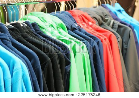 row of multi colored outdoor jackets in a store, hanging on a clothes rail