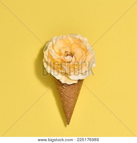 Ice Cream Cone with Yellow Flower. Creative Minimal. Yellow Rose, Bright Color. Spring Summer Floral concept. Trendy fashion Style. Art Vintage